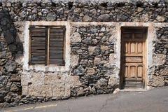 有木门和自然石门面的老房子 免版税库存照片
