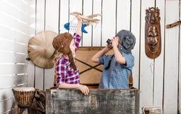 有木飞机在手中和男孩的小女孩试验帽子的 免版税库存图片