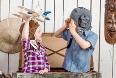 有木飞机在手中和男孩的小女孩试验帽子的 免版税图库摄影