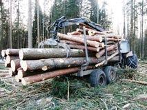 有木头充分的拖车的拖拉机  免版税库存图片