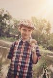 有木结尾杆的小男孩由池塘 库存图片