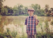 有木结尾杆的小男孩由池塘 免版税图库摄影