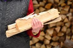 有木柴的老妇人在手上在村庄 免版税图库摄影