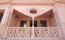 有木细长立柱的异常的桃红色19世纪阳台在downt 库存照片