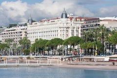 有未知的人民的散步戛纳和著名卡尔顿旅馆的frontview在戛纳,法国 免版税库存图片