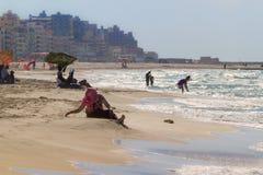 有未认出的当地的人民地方海滩的基于在2014年10月13日的一个晴朗的夏日在亚历山大,埃及 免版税图库摄影