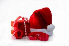 有末端箱子和丝带的圣诞老人帽子 图库摄影