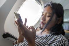 有机动性的一名妇女在一架飞行的飞机上 库存照片