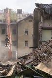 有机器和被击毁的房子的爆破位置 免版税库存图片