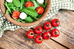 有机成熟西红柿和木碗分支用素食健康沙拉用蕃茄、无盐干酪乳酪和芝麻菜 免版税库存照片