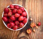 有机本地出产的樱桃和石头在葡萄酒陶瓷碗,在木背景 免版税库存图片