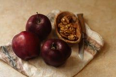 有机果子和坚果 健康快餐 红色苹果和核桃与餐巾在米黄背景 免版税库存图片