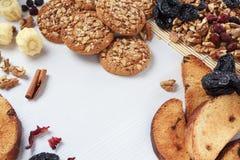 有机燕麦曲奇饼、核桃、面包干和糖果在白色桌上 免版税库存图片