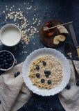有机燕麦粥粥用蓝莓、香蕉、蜂蜜和牛奶在黑暗的石桌上,健康生活方式和饮食概念 免版税库存照片