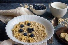 有机燕麦粥粥用蓝莓、香蕉、蜂蜜和牛奶在黑暗的石桌上,健康生活方式和饮食概念 免版税库存图片