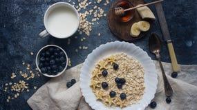 有机燕麦粥粥用蓝莓、香蕉、蜂蜜和牛奶在黑暗的石桌上 库存图片