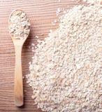 有机燕麦粥,燕麦堆剥落与在木背景的木匙子 免版税库存照片