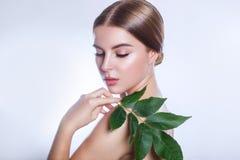 有机的化妆用品 与绿色叶子、概念护肤的或有机化妆用品的美丽的妇女面孔画象 图库摄影