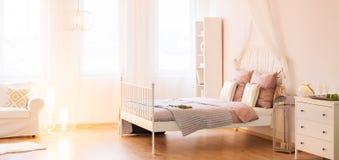 有机盖床的时髦卧室 免版税库存图片