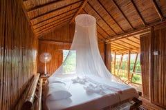 有机盖床的,装饰的竹子农村样式卧室 非常流行音乐 免版税库存图片