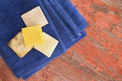 有机肥皂酒吧在一块新鲜的干净的蓝色毛巾的 图库摄影