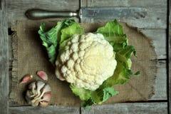 有机花椰菜和大蒜在葡萄酒背景 免版税图库摄影
