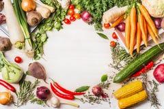 有机菜品种烹调在白色木背景,顶视图,框架的鲜美素食主义者或素食主义者的 免版税库存图片