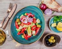 有机菜希腊沙拉用蕃茄、黄瓜、红洋葱、橄榄、希腊白软干酪和杯在木背景的酒 库存图片