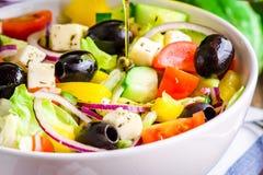 有机蕃茄、黄瓜、红洋葱、橄榄和希腊白软干酪特写镜头希腊沙拉  免版税图库摄影