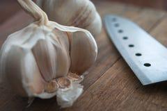 有机食品准备,烹调概念:未加工的大蒜电灯泡头,在土气木桌背景的刀子 图库摄影