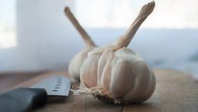 有机食品准备,烹调概念:未加工的大蒜电灯泡头,在土气木桌背景的刀子 免版税库存照片