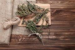 有机麝香草、麻线、粗麻布织品和切板在木 库存照片