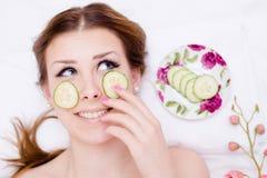 有机绿色自然温泉治疗:获得愉快的美丽的白肤金发的小姐应用切片黄瓜的乐趣于她的面孔皮肤 免版税库存图片