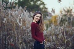 有杂乱白肤金发的长的头发的微笑的年轻美丽的妇女女孩在室外的大风天在日落,看在照相机 库存照片