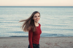 有杂乱长的头发的微笑的笑的无忧无虑的白白种人年轻美丽的妇女在室外的大风天在海滩的日落 免版税库存图片