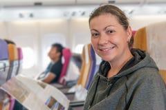 有杂志的愉快的飞机乘客在椅子微笑在f期间的 免版税库存图片