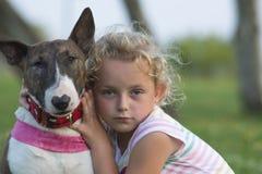 有杂种犬的白肤金发的儿童女孩 免版税库存图片