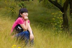 有杂草的一个沉思女孩 图库摄影