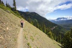 有杆的女性远足者在山土坎道路 免版税库存图片