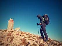 有杆的游人和背包走到山峰 对山顶的前步 免版税图库摄影