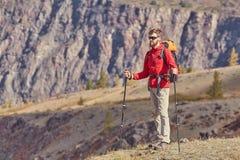 有杆的高背包徒步旅行者在手中 免版税库存图片