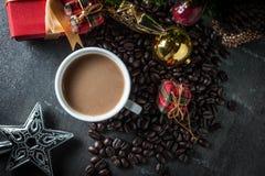 有杉木brench的咖啡杯和圣诞节玩具在黑石背景 顶视图 库存图片