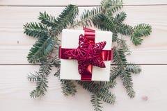 有杉树的一个礼物盒在轻的木背景分支 免版税库存照片