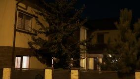 有杉树的聪明的房子从打开住宅的邻里点燃,当所有者在晚上来在家里面- 股票视频