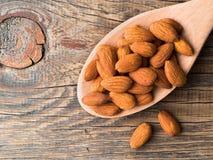 有杏仁几枚坚果的大木匙子在木的 免版税库存照片