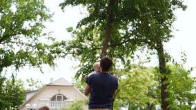 有村庄的美丽的乡下在背景 绿色公园 跑到他的父亲的小白肤金发的男孩 他捉住他 股票录像