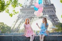 有束的两个女孩在埃佛尔铁塔前面的气球 库存照片