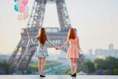 有束的两个女孩在埃佛尔铁塔前面的气球 免版税库存照片