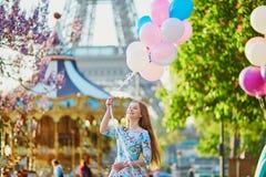 有束的女孩在埃佛尔铁塔前面的气球在巴黎 库存照片