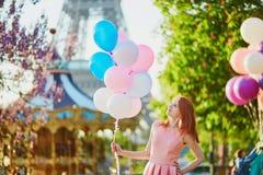 有束的女孩在埃佛尔铁塔前面的气球在巴黎 免版税库存图片